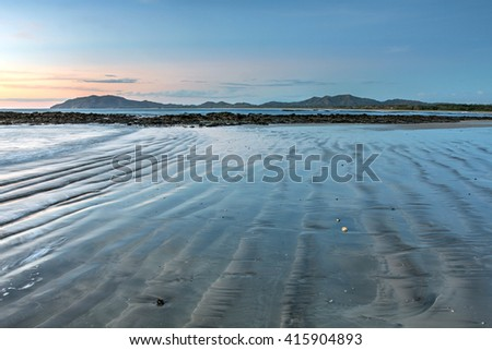 Tamarindo beach at sunset and low tide in Guanacaste, Costa Rica. - stock photo