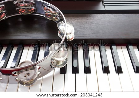 Tambourine on piano keys. Music concept and background. - stock photo