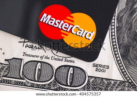 Tambov, Russian Federation - April 02, 2016 Mastercard logo on credit card and one hundred dollar bill. Studio shot. - stock photo