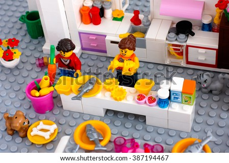 Tambov, Russian Federation - August 29, 2015 Cooking dinner. Lego domestic kitchen with woman cooking dinner, girl taking carrot, dog eating bones, cat sitting on floor. Custom set. Studio shot. - stock photo