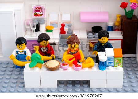 Tambov, Russian Federation - August 29, 2015 Lego family in domestic kitchen. Woman is cooking dessert. Custom set. Studio shot. - stock photo