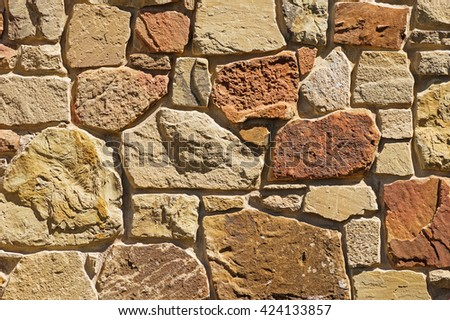 tan and reddish stone wall background texture  - stock photo