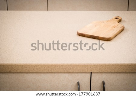 Tan kitchen counter with cutting board minimalist style - stock photo