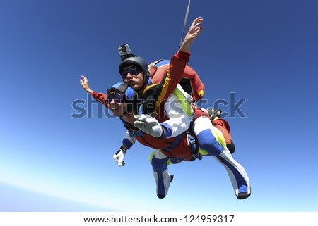 Tandem jump. The girl with the instructor in free-fall. - stock photo