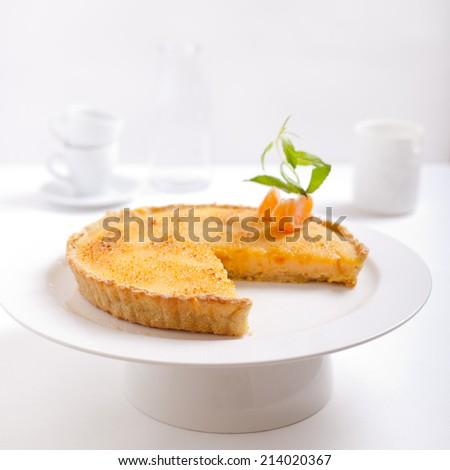 Tangerine creme brulee tart on a white background with fresh mint leaves and piece of tangerine - stock photo