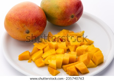 Tangerine, diced fruit flesh of a ripe mango placed on a white plate. Two whole mangos behind. White background. Medium wide depth of field. - stock photo