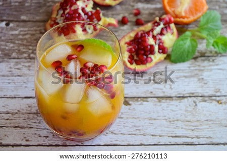Tangerine juice with pomegranate and mint leaves in a glass full of ice cubes - stock photo