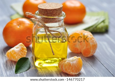 tangerine oil in a glass bottle with fresh tangerine ���®��� wooden background - stock photo