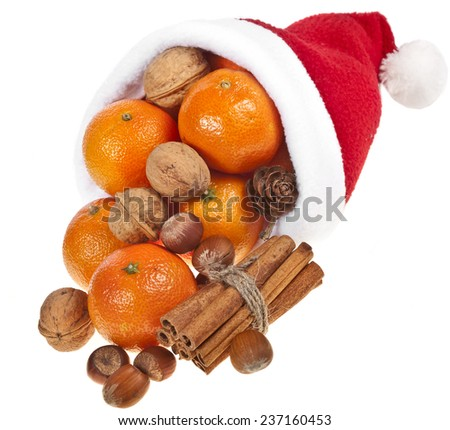 tangerines and nuts in a Santa hat  isolated on a white background - stock photo