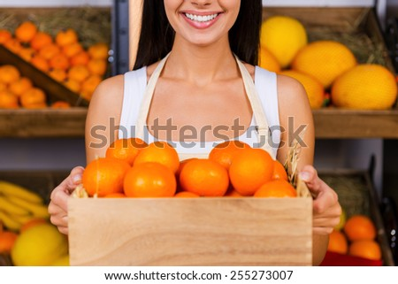 Tangerines for you. Cropped image of beautiful young woman in apron holding wooden container with tangerines and smiling while standing in grocery store with variety of fruits in the background  - stock photo