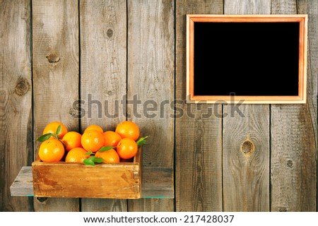 Tangerines in a box on a wooden shelf. A framework on a wooden background. - stock photo