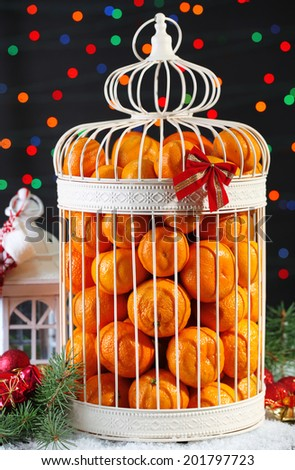 Tangerines in decorative cage with Christmas decor, on shiny background - stock photo