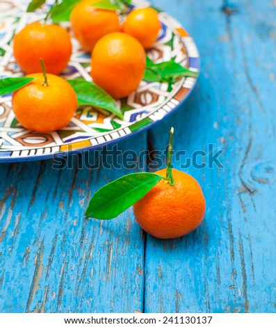 tangerines  with leaves in plate  on wooden background, in blue color - stock photo