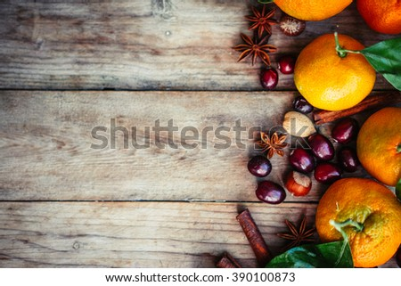 Tangerines with nuts,cranberries and cinnamon on rustic wooden background - stock photo
