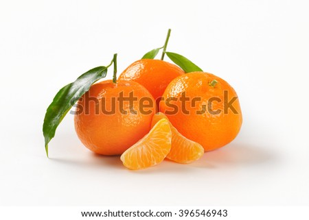 tangerines with separated segments on white background - stock photo