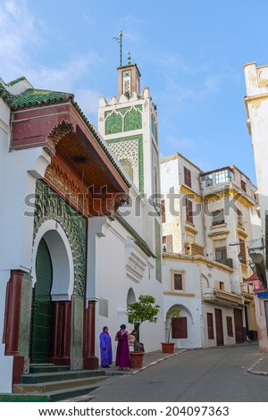 TANGIER, MOROCCO - MARCH 22, 2014: Street view of old Medina area in Tangier, Morocco. Arabic women stand near old mosque - stock photo