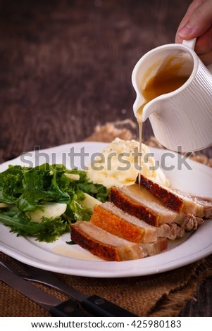 tangy apple gravy pouring on Garlic n thyme crispy crackling roasted pork belly served with butter cream mash potato and fresh salad against dark wooden background - stock photo