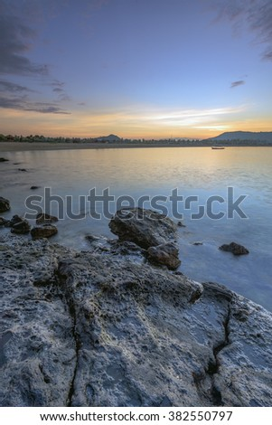 Tanjung Ann Beach, Lombok, Indonesia. Taken using long exposure during sunrise. Motion blur due to slow shutter speed. Caption space area. - stock photo