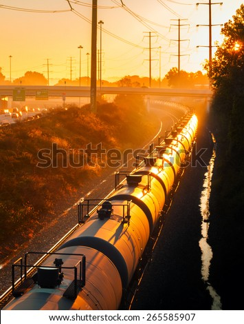 Tank cars of a long freight train glow orange in the light of the rising sun - stock photo