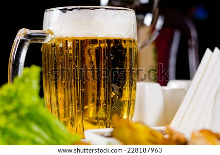 Tankard of chilled beer with a frothy head served in a restaurant with a salad lunch for a refreshing beverage - stock photo