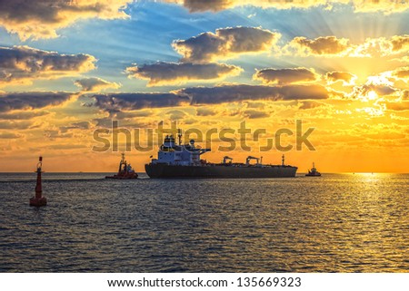 Tanker at sunset putting out to sea. - stock photo