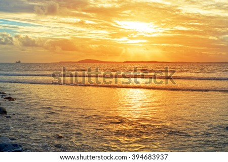 tanker in the shannon estuary near ballybunion on the wild atlantic way ireland with an orange sunset - stock photo