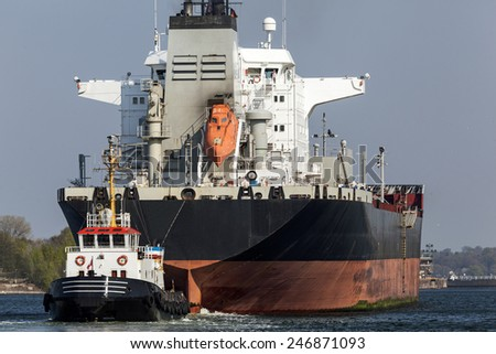 Tanker ship and tug boat on Kiel Canal, Germany - stock photo