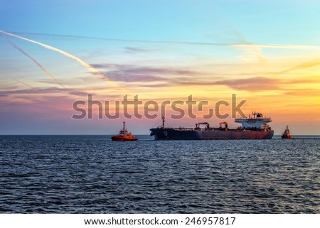Tanker ship with escorting tugs on sea at sunrise.  - stock photo