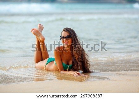 tanned beautiful brunette laying on tropical beach - stock photo