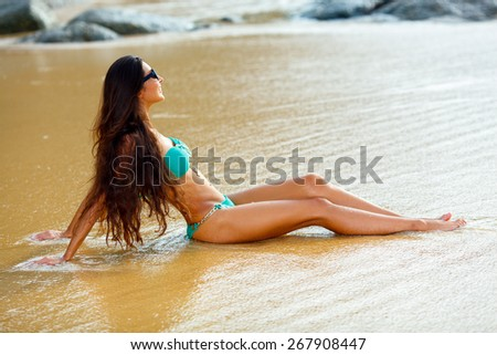 tanned beautiful brunette sitting on tropical beach - stock photo