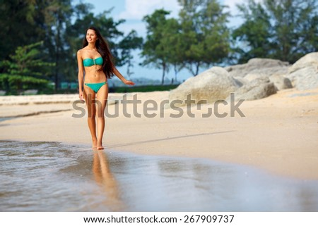 tanned beautiful brunette walking along the tropical beach - stock photo