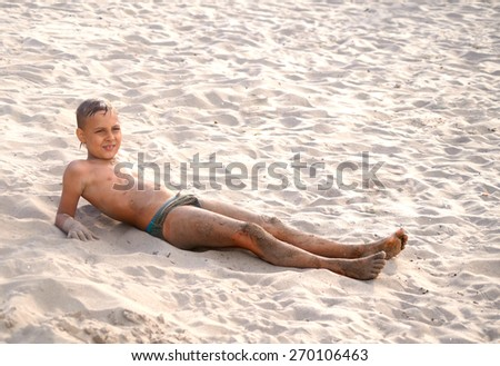 tanned boy playing in the sand near the water - stock photo