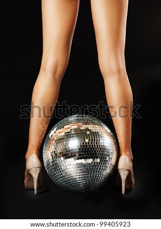 Tanned female legs with disco ball over black background - stock photo