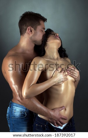 Tanned passionate lovers embracing in studio - stock photo