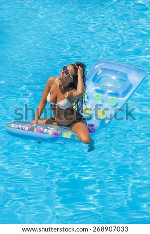 Tanned woman relaxing at the swimming pool - stock photo