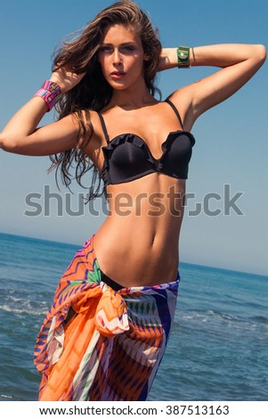 tanned young woman in bikini top and colorful sarong on sea beach sunny summer day - stock photo
