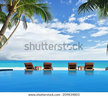 Tanning beds beside blue pool with tropical seascape view -- Tropical vacations concept  - stock photo