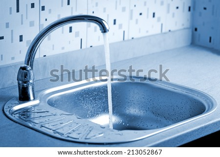 Tap water flowing to a sink - stock photo