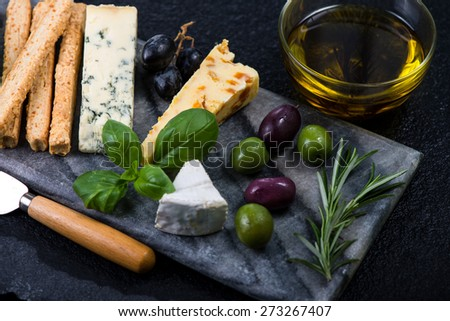 Tapas style cheese selection with olives,grapes and herbs on board from above - stock photo