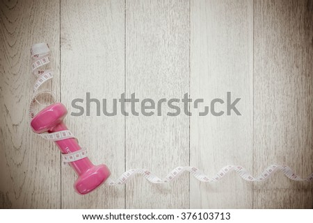 Tape and dumbbells fitness on wooden background. Different tools for sport, Vintage Style. - stock photo