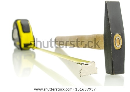 Tape measure and hammer on white desk with reflection.  - stock photo