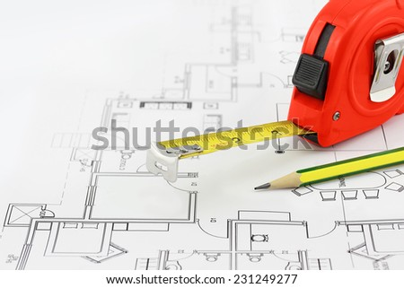 Tape measure and pencil over a construction plan drawing - stock photo