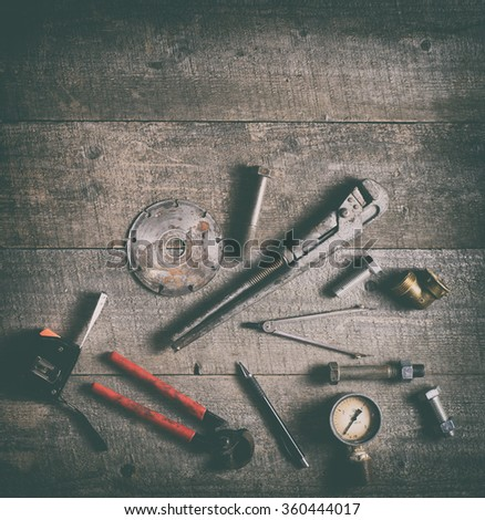 Tape-measure, internal screws, bolts, manometer, diamond wheel, tools on old wooden table. - stock photo