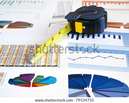 Tape measure on the investment charts. - stock photo