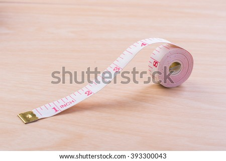 Tape measure on wooden background. - stock photo