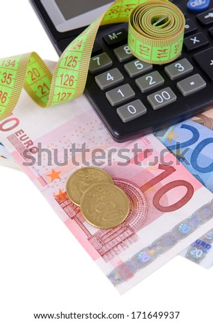 Tape measure with money and calculator close-up - stock photo