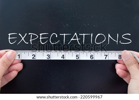 Tape measuring expectations on a chalk board  - stock photo