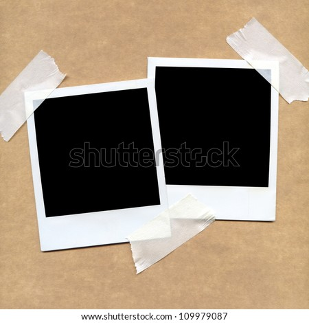 Taped polaroid style photo frames on cardboard - stock photo