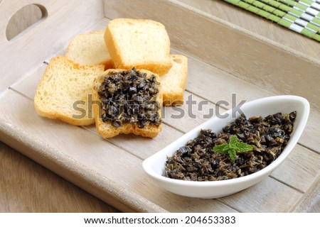 Tapenade, a traditional French dish consisting of pureed or finely chopped olives, capers, anchovies and olive oil  - stock photo