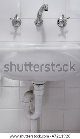 Taps and basin in a bathroom - stock photo